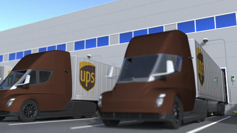 Electric semi-trailer trucks with UPS logo being loaded or unloaded at warehouse GIF