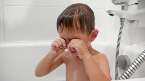 Closeup slow motion video of little boy rubbing eyes and feeling pain in eyes Live Action