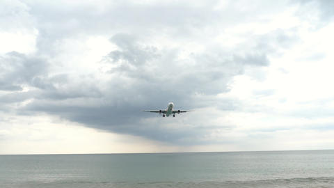 Widebody airplane approaching over ocean GIF