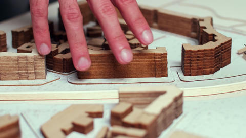 Close up of architect hand moving over city model GIF