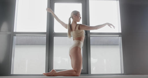 Attractive young blonde woman makes acrobatic gymnastic tricks in slow motion on Live Action