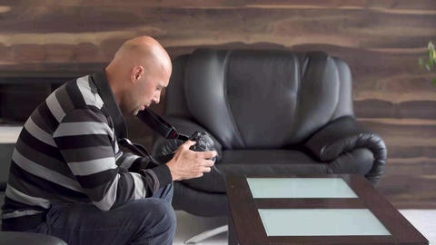 man photographer checks the camera and does test shots in the living room on the Live Action