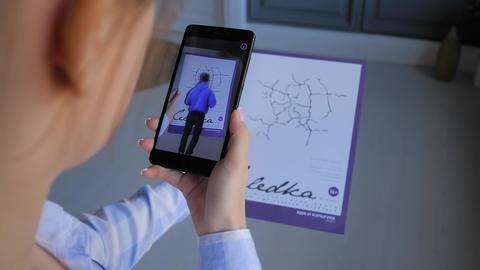 Woman holding magazine and using smartphone with AR application Acción en vivo