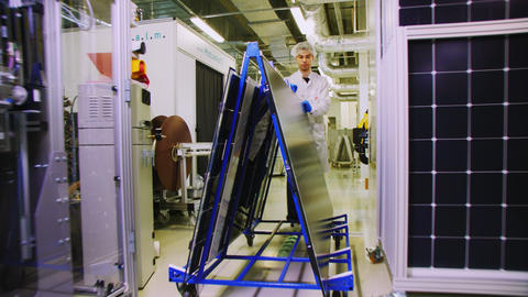 employee carries rack with solar panels along plant workshop Live Action