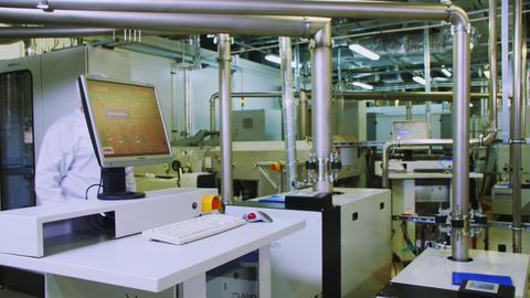 employee comes to computer at solar panel production plant Acción en vivo