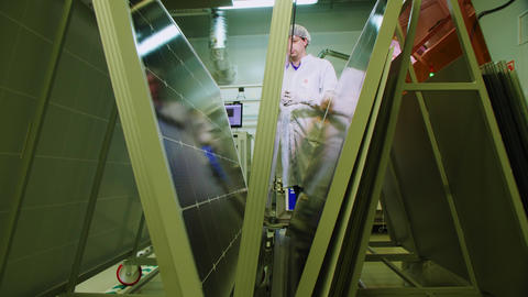 employee inspects solar panels in production plant workshop Live Action