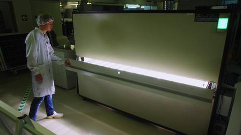 worker opens machine for solar panels production at plant Acción en vivo