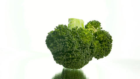 Closeup slow motion video of broccoli piece falling on wet reflective surface Live Action