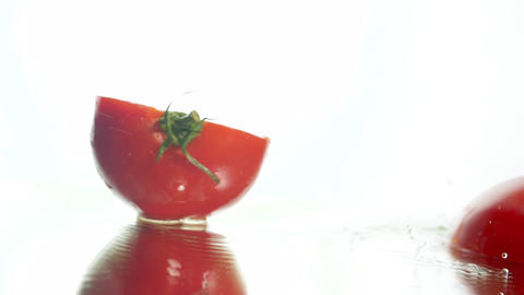 Closeup slow motion video of fresh red tomato falling on wet reflective surface Live Action