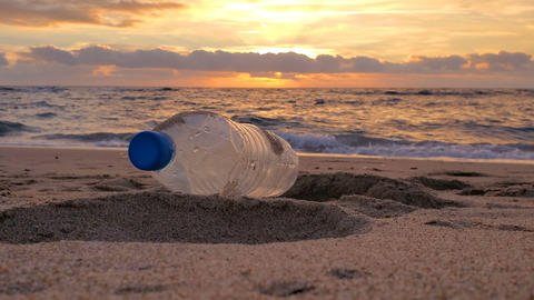 Plastic bottle trash on sandy sea shore sunset motion,polluted nature,cilento Live Action