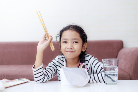 Little Asian girl sitting at white table to eating instant noodl フォト