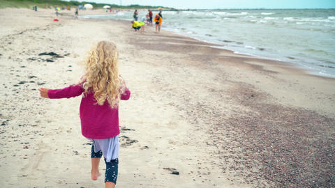 Blond girl running through coastline sea shore. Beautiful active child have fun Live Action