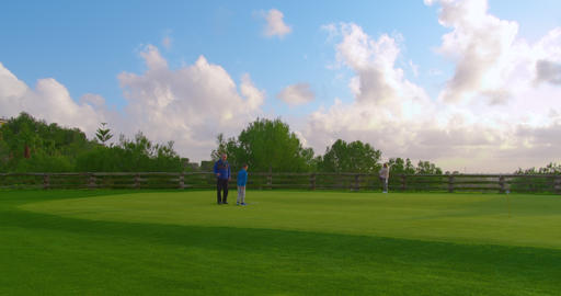 Granddad with his grandson golfers playing on perfect golf course. Timelapse Live Action