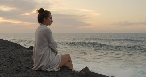 Romantic white european girl sitting on the big huge rock. Ocean tide at sunset Live Action