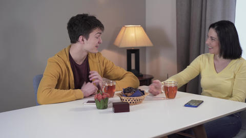 Portrait of cheerful Caucasian mother and teen son sitting at the table at home Live Action
