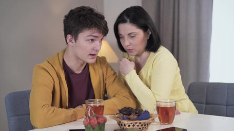 Brunette Caucasian woman whispering shocking information on ear of teenage boy Live Action