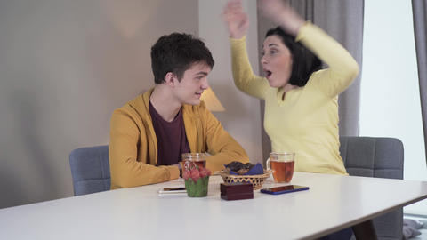 Middle shot of joyful young Caucasian woman telling jokes to teenage boy as Live Action