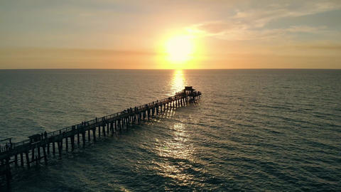 Flying along a wooden long pier at sunset time Live Action