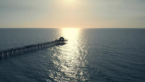 Sunset over ocean or sea, Drone flying above pier Live Action