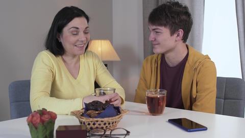 Teenage Caucasian brunette boy kissing mom on cheek. Positive son spending Live Action