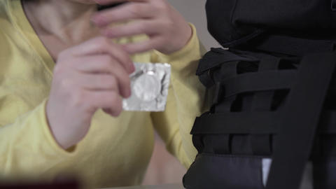 Close-up of female Caucasian hands taking out condom from backpack. Worried Live Action