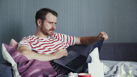 Sick bearded man using laptop to watch a movie or video GIF