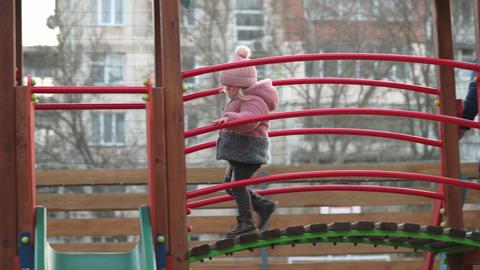 Toddler girl slides down the children's slide at local playground Live Action