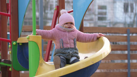 Toddler girl slides down the helical children's slide at local playground Live Action