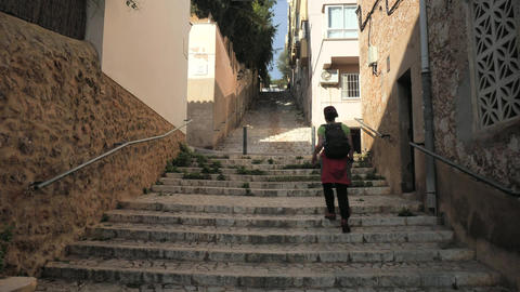 Woman rising up on stony staircase in historical old town. Girl backpacker walks by steps to Live Action