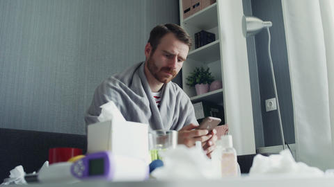 Young man sitting on sofa use phone coughs in home drink tea feel sad unhappy GIF