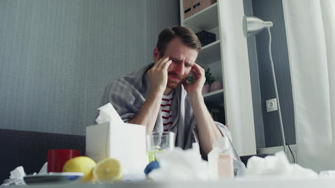 Sick man is suffering from severe headache touching his head massaging temples GIF