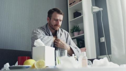 Sick man with flu sitting on sofa at home. Ill young man with cold checking GIF