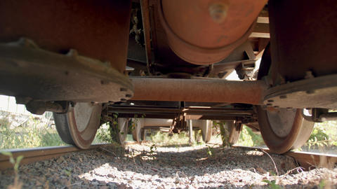 4k dolly video of cameray moving under old rusty cargo train car on abandoned Live Action