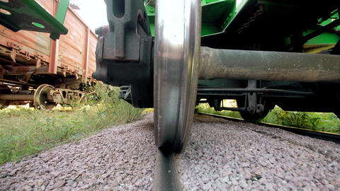 4k dolly video of looking underneath heavy cargo train car on station. Concept Live Action