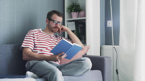 Caucasian young good looking man with glasses reading a book Live Action