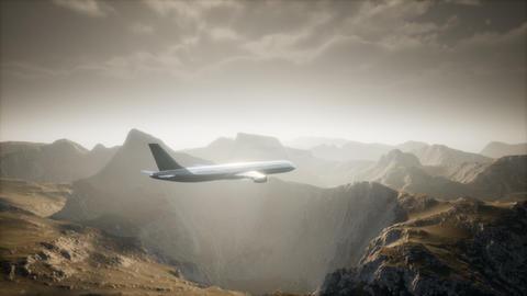 Passenger aircraft over mountain landscape Live Action
