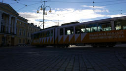 Car and tram pass by Senate Square, high contrast evening sunlight Footage