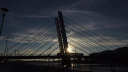Asymmetric cable-stayed bridge shadow silhouette at evening, tram car pass over Live Action