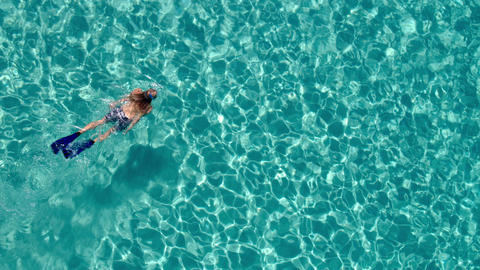 Aerial - Woman snorkeling in crystal clear waters of luxury travel destination Footage