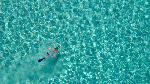 Aerial - Woman in board shorts snorkeling underwater in crystal clear waters Footage