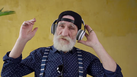 Handsome elated stylish bearded 70-aged man in headphones listening beautiful Live Action