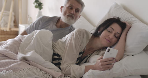 Jealous senior Caucasian man looking over shoulder of wife at smartphone screen Live Action