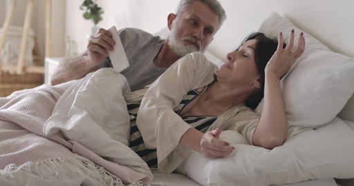 Furious Caucasian senior man taking away wife's smartphone in bed. Husband Live Action