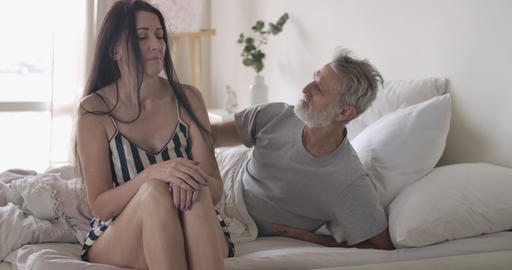 Handsome senior Caucasian man touching wife's hair, but upset woman moving his Live Action