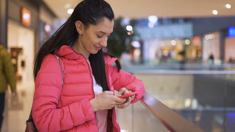 Concentrated girl using smartphone in the mall Live Action