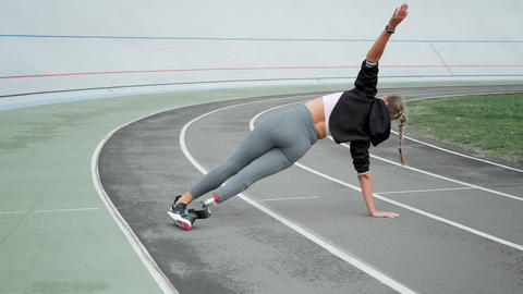 Disabled athlete standing in plank on hand at track. Girl practicing yoga Live Action