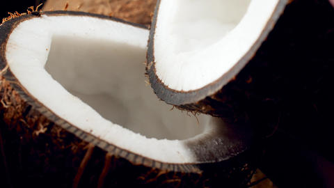 Slow motion closeup video of water slowly pouring from one coconut half into Live Action