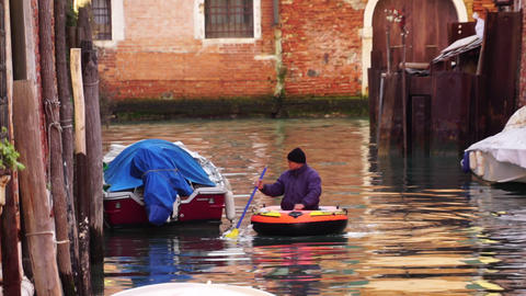 Venice / Italy - January 7 2019: Man in an inflatable dinghy boat on a canal in Venice Italy in Live Action