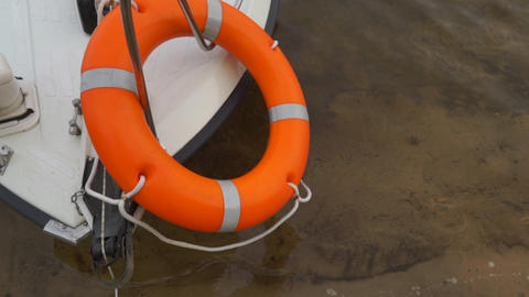 Lifebuoy hanging on a boat moored at the shore Live Action