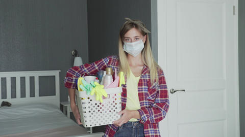 Woman with mask on face and Basket full of sponges and household chemicals look GIF